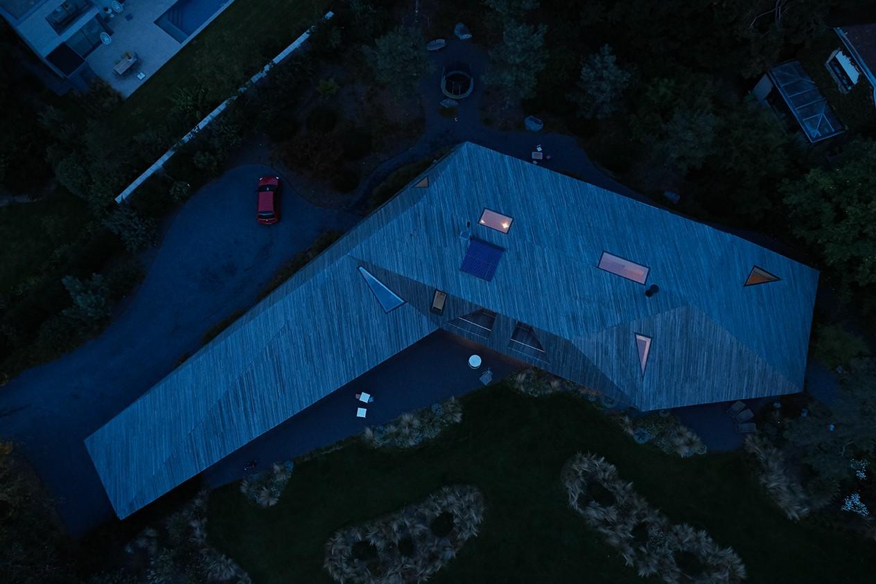 Семейный дом под скульптурной деревянной крышей