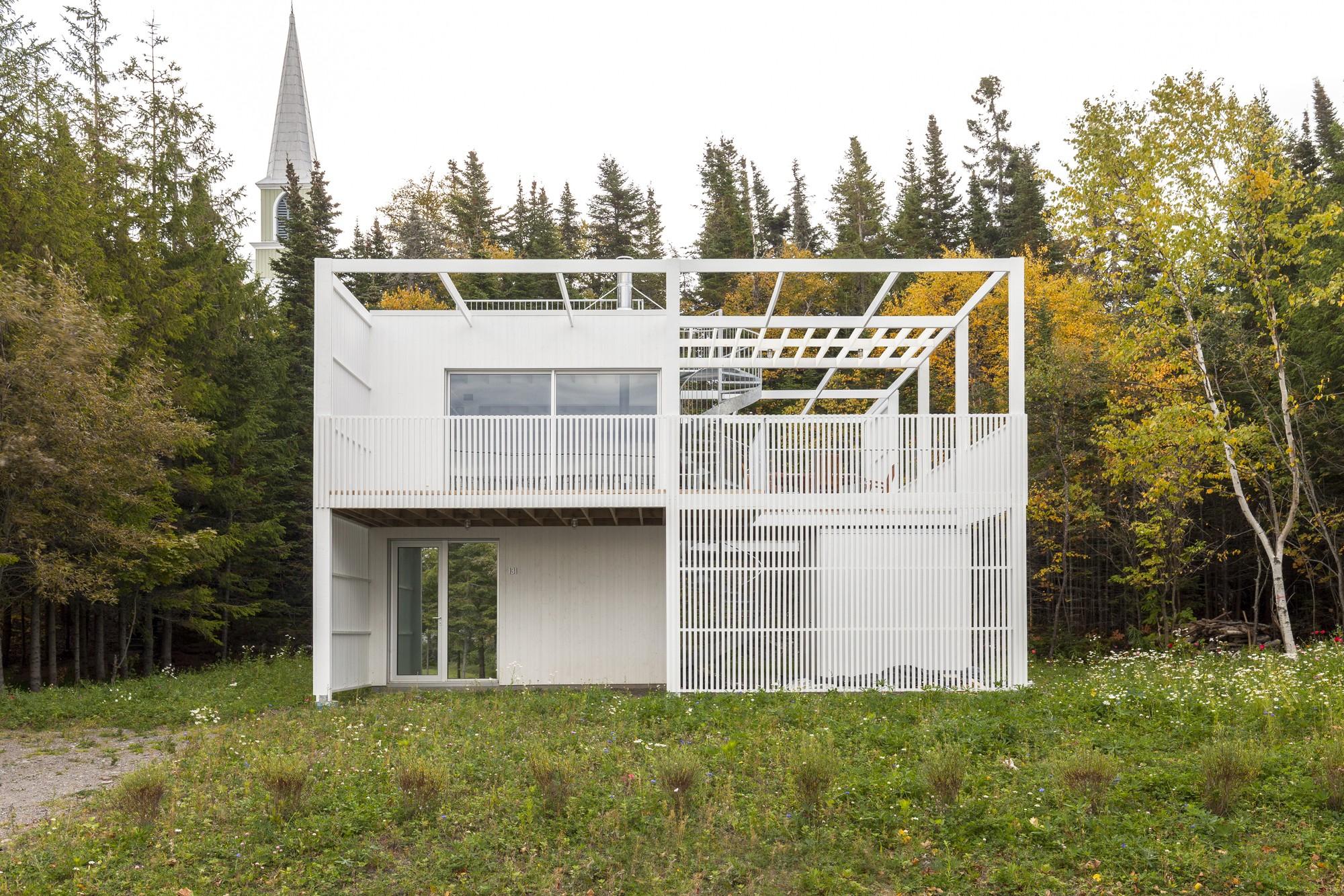 Геометрический дом с фасадом-фильтром из белых ламелей