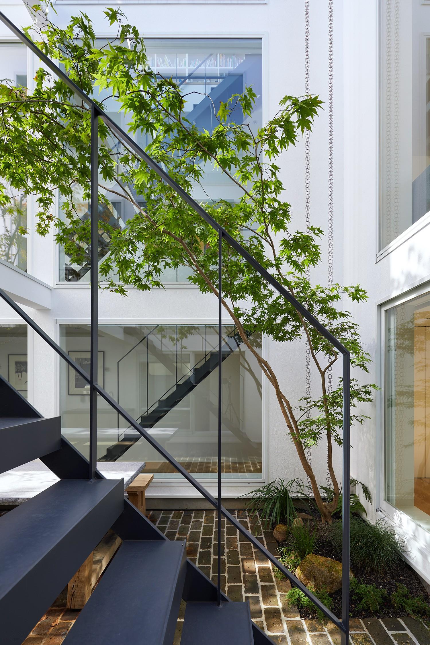 Семейный дом, соединенный двором-атриумом с пышной растительностью и зоной-барбекю
