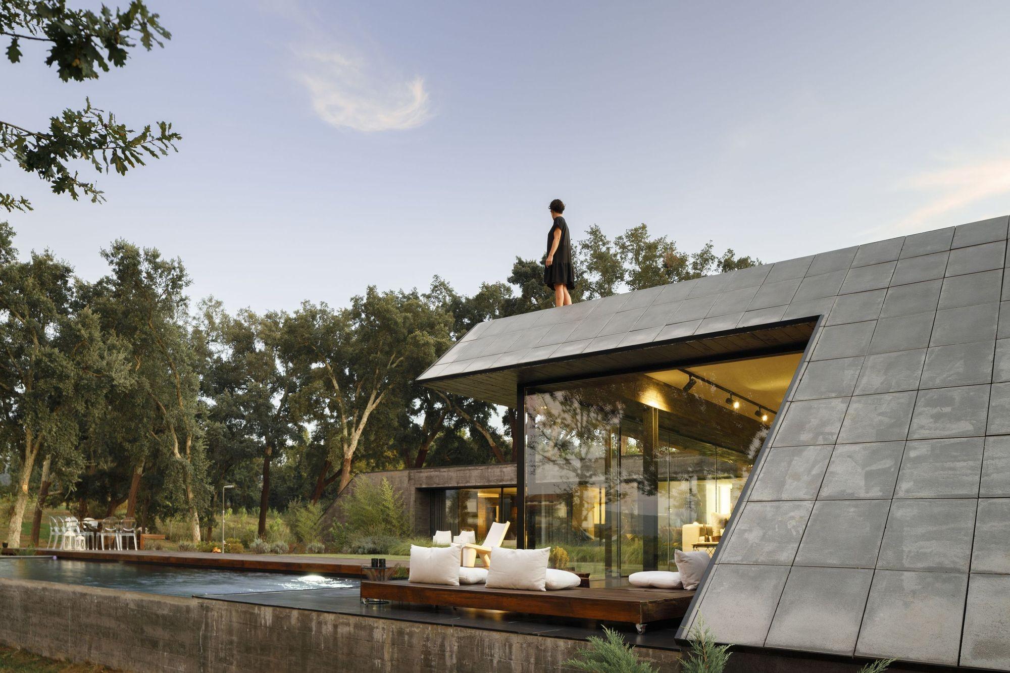 Бетонный дом с креативным дизайном, интегрированный в природный ландшафт