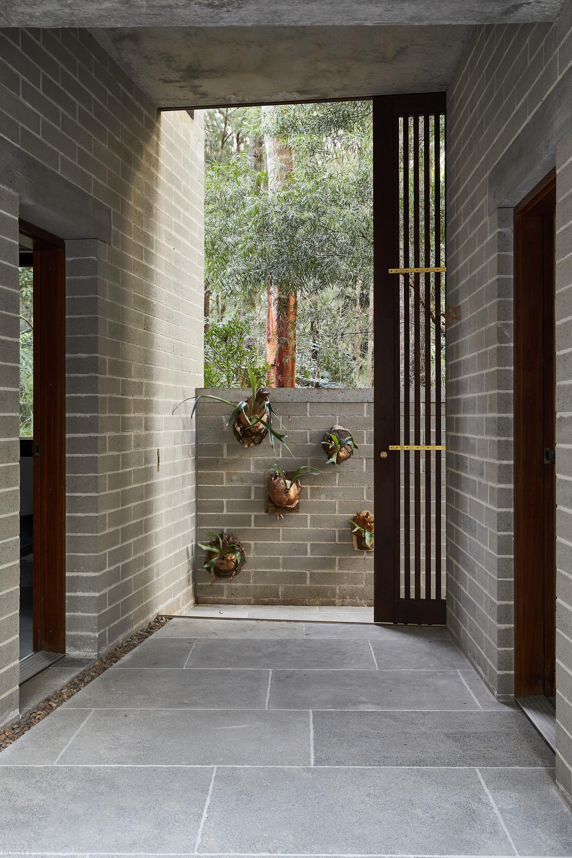 Бетонный скульптурный дом с внутренними двориками, открытыми в небо